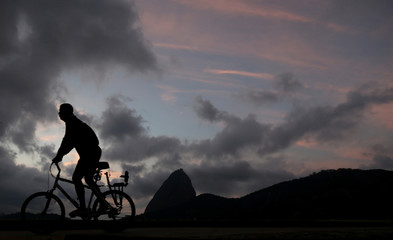 A man rides a bicycle, with Sugar Loaf mountain in the background, in Rio de Janeiro