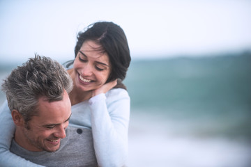 A beautiful couple in their forties  walks on the beach