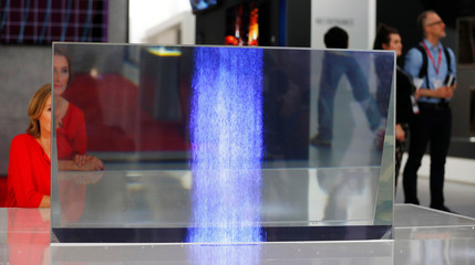 A woman sits behind a transparent OLED tv from Panasonic at the IFA Electronics show in Berlin