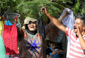 A salesman and a woman sell clothes at a street market in Cairo