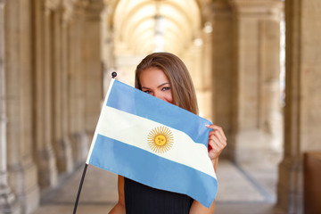 Happy young woman covering her face by flag of Argentina