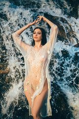 A young princess in a vintage dress swims in a waterfall. Creative colors