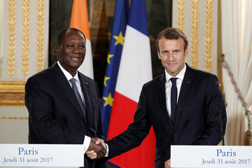 French President Emmanuel Macron shakes hands with Ivory Coast President Alassane Ouattara after a joint press conference at the Elysee Palace in Paris