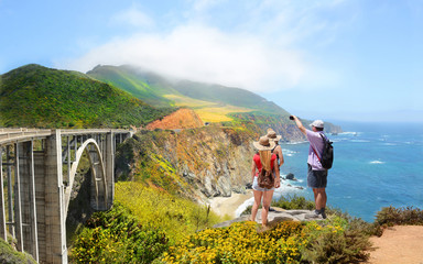 Family looking at beautiful summer mountains landscape, on hiking trip. Father taking photos  of  Bixby Bridge with phone. Big Sur, California, USA.