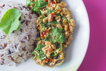 Thai style fried chilly basil with minced pork and preserved egg and mixed rice meal ready for serving