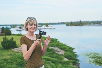 Woman filming with small personal camera a park with a river