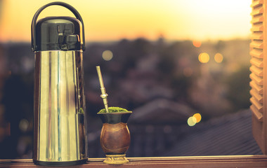 Thermal bottle and chimarrao in the window at sunset - Drink from southern Brazil.