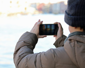 boy takes pictures with the modern smartphone during a winter tr