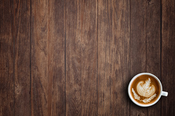 A cup of hot latte art or cappuccino coffee on wooden table. Top view