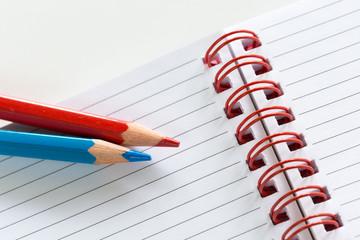 Pastello rosso e azzurro su notes a righe con spirale rossa