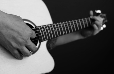 Closeup of man playing guitar in black and white tone