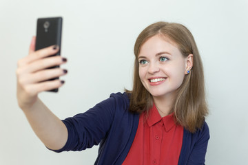 Young woman with a smart phone makes selfie