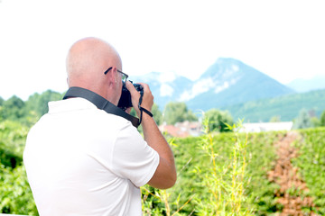 mature man photographs the mountains