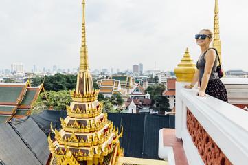 Young woman explores Wat Ratchanatdaram - Buddhist temple (wat) located in Phra Nakhon district, Bangkok, Thailand