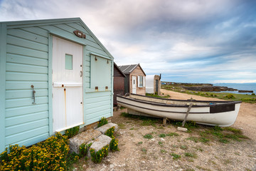 Beach huts and a boat under a moody sky at Portland Bill near Weymouth on the Dorset coast