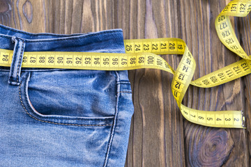 Healthy lifestyle and nutrition concept. Blue jeans with a measuring tape instead of a belt. Close up of jeans with a measuring tape around the waist.