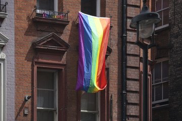 The rainbow flag is hung from the window in the Soho