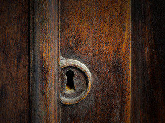 Detail of a dusty old keyhole in the door of a antique cabinet. The wood has warm tones and the keyhole is covered in dust and dirt