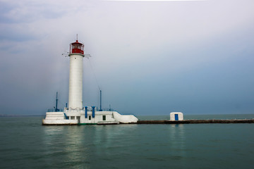 White lighthouse with a red tip in the sea.