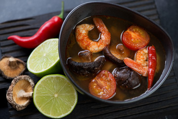 Close-up of spicy Tom Yum Thai soup with shrimps, shiitake mushrooms and red chili peppers, elevated view
