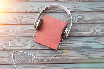 Audio book concept. Headphones and old book over wooden table.