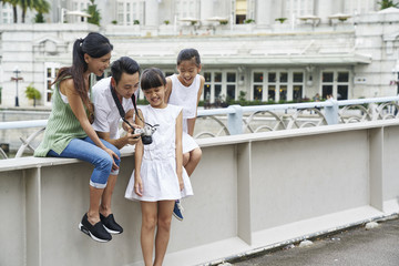 Smiling Happy family reviewing the images they took at Cavenagh Bridge, Singapore