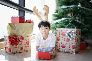 Boy with Christmas presents on the floor under a tree