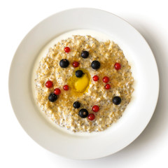 White bowl of oats porridge with chia seeds, berries, butter, brown sugar and milk solated on white from above.