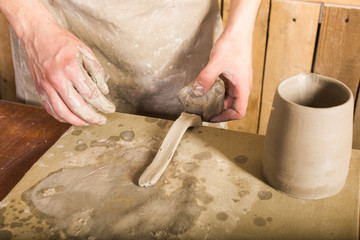 pottery, stoneware, ceramics art concept - closeup on master hands working with some piece of clay, male stand at a workshop near table, craftsman fingers forming the handle from raw fireclay