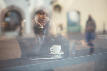 Young black woman talking on phone in cafe