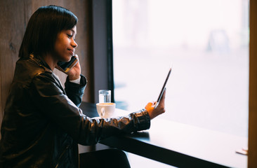 Young black woman talking on phone using tablet computer in coffee shop