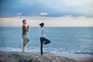 Beautiful couple practicing yoga on the beach at sunrise