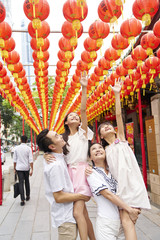 Cheerful family of four having fun with Chinese New Year decorations