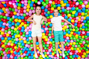 Boy and girl playing in colorful balls