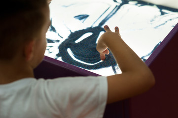 A boy and a girl are painting with sand. Sand animation