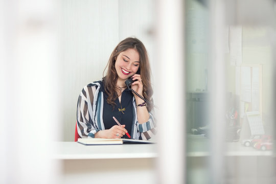 Cheerful young businesswoman is talking on the phone while working at her desk