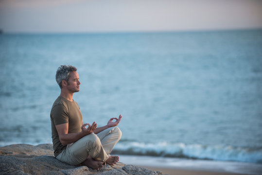 gray-haired man practicing yoga on the beach at sunrise