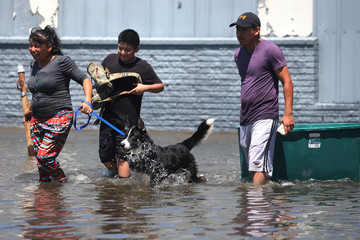 People walk with their possessions out of a flooded area of Port Arthur, Texas