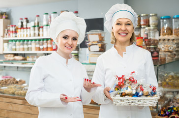 Portrait of female baker with pastry smiling in bakery