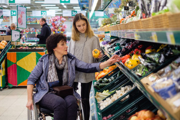 Girl helping disabled mothter in a grocery store.