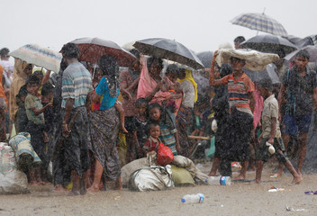 Rohingya refugees stand in an open area during heavy rain as they are held by the Border Guard Bangladesh (BGB) after illegally crossing the border, in Teknaf