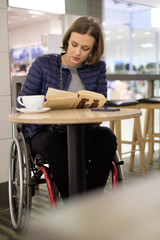 Physically challenged woman reading in a cafe