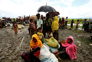 Rohingya refugees sit with their belongings in the mud as they are held by the Border Guard Bangladesh (BGB) in an open area after illegally crossing the border, in Teknaf