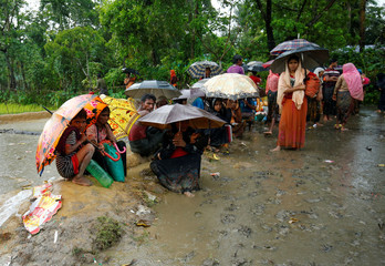 Rohingya refugee people sit in the mud during heavy rain, as they are held by Border Guard Bangladesh (BGB) in an open area after crossing the border, in Teknaf