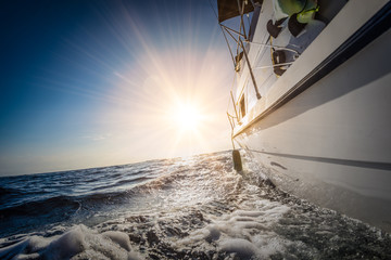 Boat sailing on water surface of blue ocean into the sun