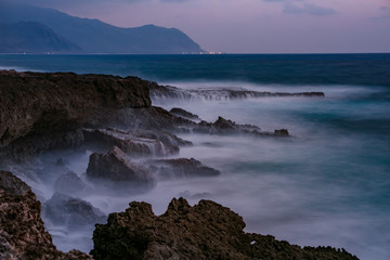 Night rocky shore with smooth water long exposure shot