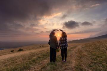 Senior couple in love on mountain at idyllic sunset