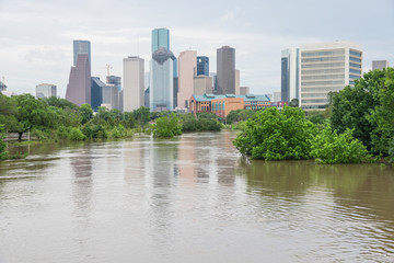High and fast water rising in Bayou River along Allen Parkway and Memorial Drive with downtown Houston in background under storm cloud sky. Heavy rains from tropical storm caused many flooded areas