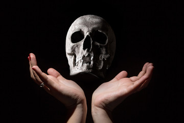 Black magic concept. Human skull between woman hands on black background.