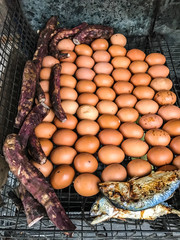 Closeup Traditional Thailand Street Food: Grilled/Roasted chicken eggs, sweet taros, mackerel fish and corn on the charcoal grill stove on the mobile market stall.